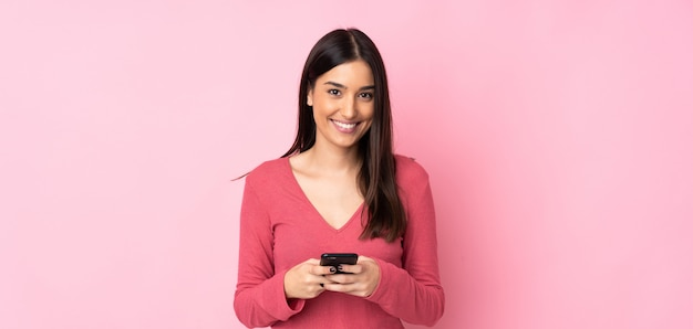 Jonge kaukasische vrouw over geïsoleerde muur die een bericht met mobiel verzendt