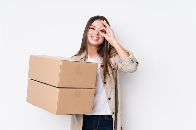 Jonge kaukasische vrouw verhuizen naar een nieuw opgewonden huis houden ok gebaar op oog.
