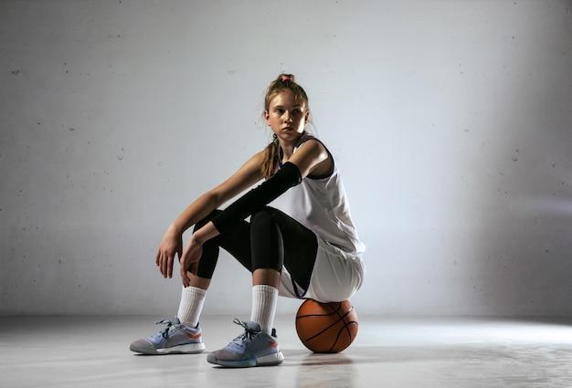 Jonge kaukasische vrouwelijke basketbalspeler van team poseren zelfverzekerd geïsoleerd op een witte muur achtergrond. concept van sport, beweging, energie en dynamische, gezonde levensstijl. training, beweging, actie.