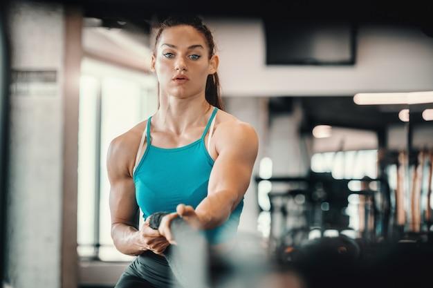 Jonge kaukasische vrouwelijke bodybuilder die kabel in gymnastiek trekt. bid niet voor een gemakkelijk leven, bid om sterker te worden.