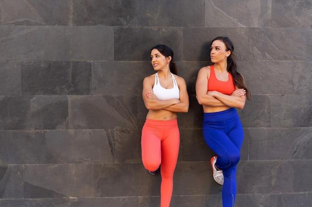 Jonge kaukasische vrouwelijke vrienden die oefeningen doen en buiten rekken - gezond levensstijlconcept