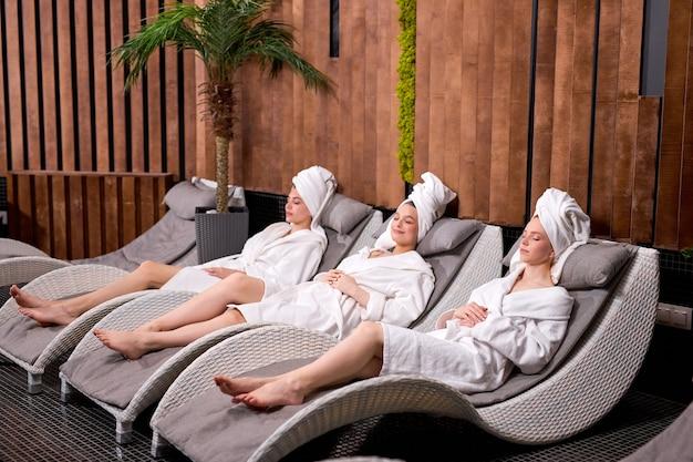 Jonge kaukasische vrouwen in badjas en handdoeken die op bed in kuuroordcentrum liggen die rust genieten van tijd
