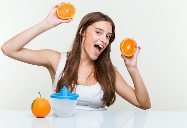 Jonge kaukasische vrouwenholding die een jus d'orange maakt