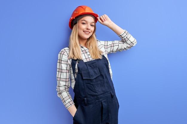 Jonge kaukasische vrouweningenieur met oranje helm die zich met positieve uitdrukking bevinden