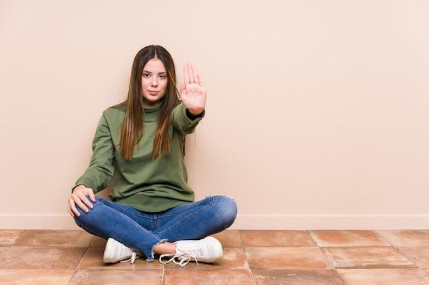 Jonge kaukasische vrouwenzitting op de geïsoleerde vloer status met uitgestrekte hand die stopbord toont, dat u verhindert.