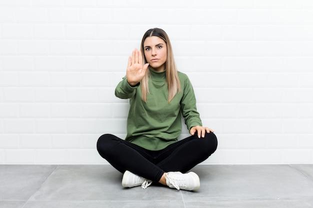 Jonge kaukasische vrouwenzitting op de vloer die zich met uitgestrekte hand bevindt die stopbord toont, dat u verhindert.