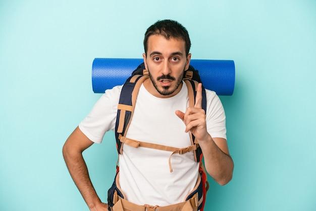 Jonge kaukasische wandelaar man geïsoleerd op blauwe achtergrond met een idee, inspiratie concept.
