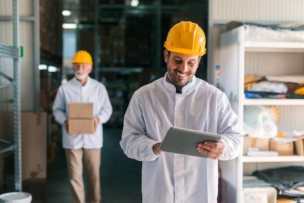 Jonge kaukasische werknemer die tablet gebruikt terwijl hij in magazijn staat.