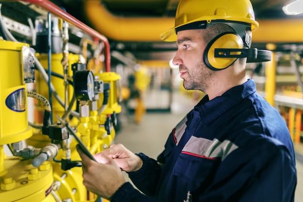 Jonge kaukasische werknemer in beschermend kostuum die tablet gebruiken terwijl het controleren van machines in verwarmingsinstallatie.