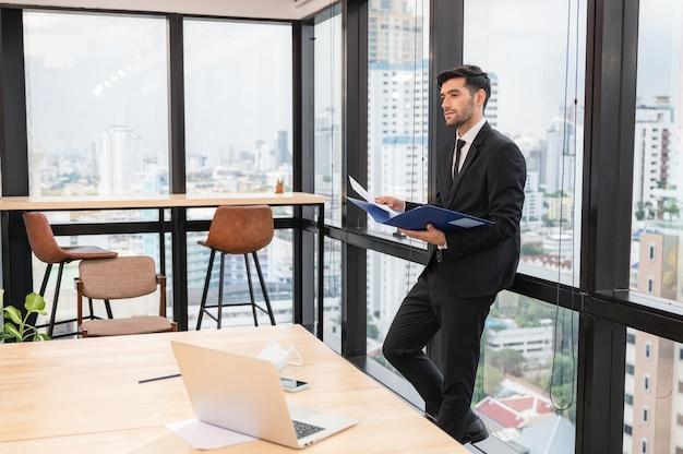 Jonge kaukasische zakenman die financieel document houdt