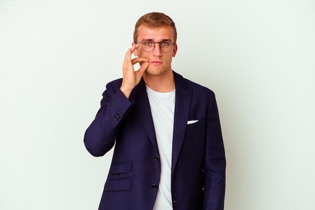 Jonge kaukasische zakenmens die op witte achtergrond met vingers op lippen wordt geïsoleerd die een geheim houden.