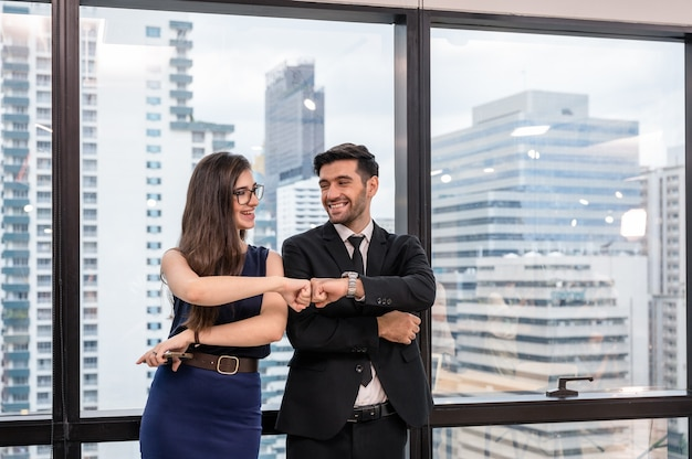 Jonge kaukasische zakenpartner die vuistbult en geluk op kantoor geeft