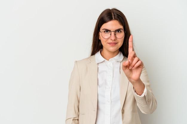 Jonge kaukasische zakenvrouw die op witte achtergrond wordt geïsoleerd die nummer één met vinger toont.