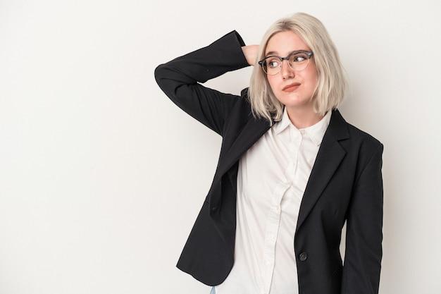 Jonge kaukasische zakenvrouw geïsoleerd op een witte achtergrond die de achterkant van het hoofd aanraakt, denkt en een keuze maakt.