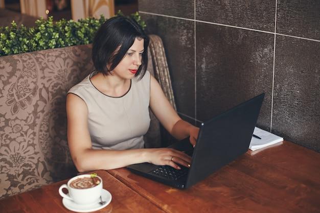 Jonge kaukasische zakenvrouw met laptop en notebook. vrouw in café