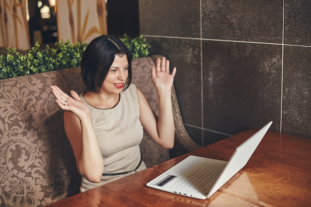 Jonge kaukasische zakenvrouw met laptop. vrouw in café