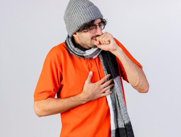 Jonge kaukasische zieke man met bril, muts en sjaal houden vuist in de buurt van mond hoesten en hand op borst met gesloten ogen geïsoleerd op witte achtergrond
