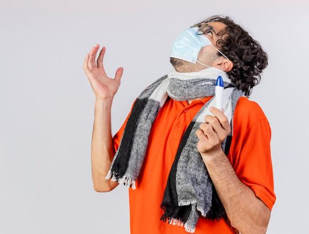 Jonge kaukasische zieke mens die bril en masker met de thermometer van de sjaalholding houdt omhoog houdend hand in lucht opzoeken die op witte achtergrond met exemplaarruimte wordt geïsoleerd