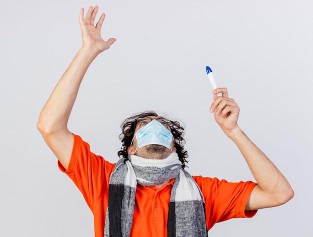 Jonge kaukasische zieke mens die glazen sjaal en masker houdt die thermometer omhoog kijkt die omhoog hand op witte achtergrond wordt geïsoleerd