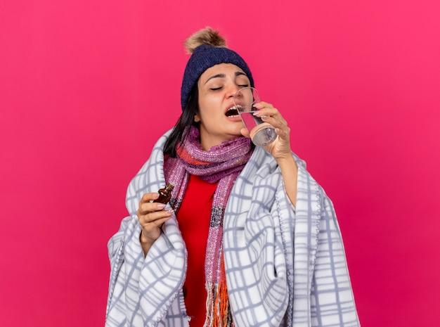 Jonge kaukasische zieke vrouw dragen winter muts en sjaal verpakt in plaid geneesmiddel in glas drinkwater gemengd met geneesmiddel uit glas met gesloten ogen geïsoleerd houden