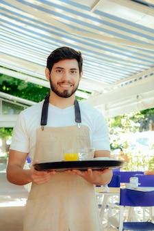 Jonge kelner die dienblad houdt.