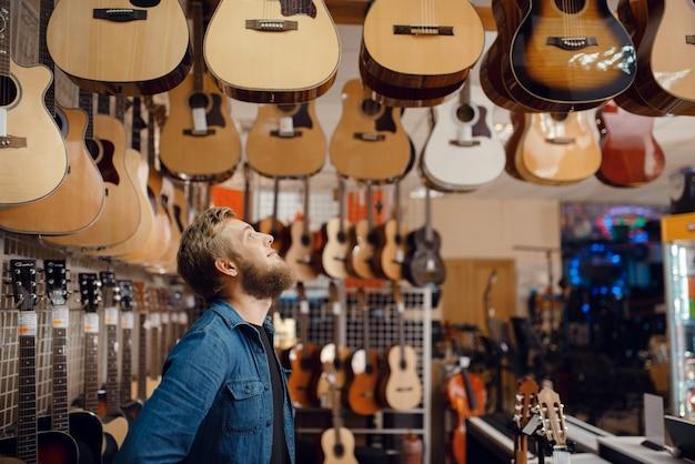 Jonge kerel akoestische gitaar kiezen in muziekwinkel