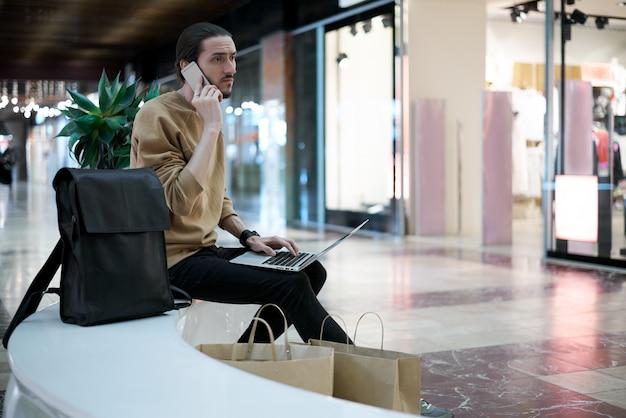Jonge kerel belt naar een vriend om te vertellen over de verkoop in het winkelcentrum