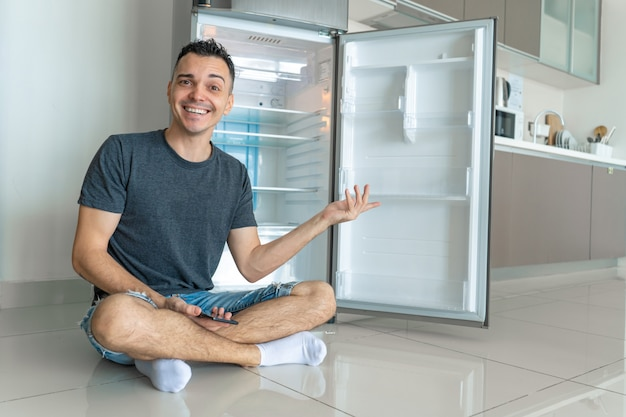 Jonge kerel dichtbij lege koelkast zonder voedsel