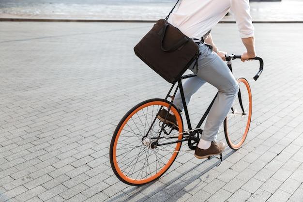 Jonge kerel die formele kleding draagt, die op fiets op stadsstraat berijdt