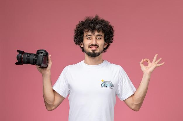 Jonge kerel die goed gebaar toont en fotocamera houdt