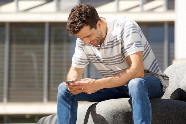 Jonge kerel die in openlucht en tekstbericht op mobiele telefoon verzendt