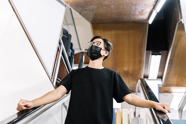 Jonge kerel die met een gezichtsmasker voor het covid-19 coronavirus winkelt