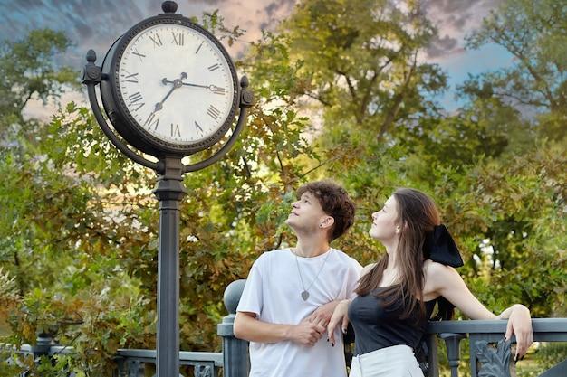 Jonge kerel en een meisje kijken naar een grote klok die op straat is geïnstalleerd.