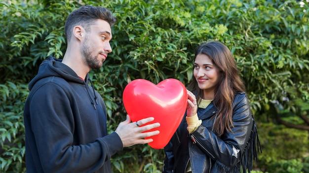 Jonge kerel en glimlachende dame met ballon in vorm van hart
