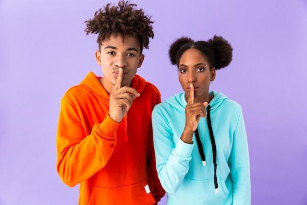 Jonge kerel en meisje die wijsvingers op lippen houden die shh betekenen, geïsoleerd over violette muur