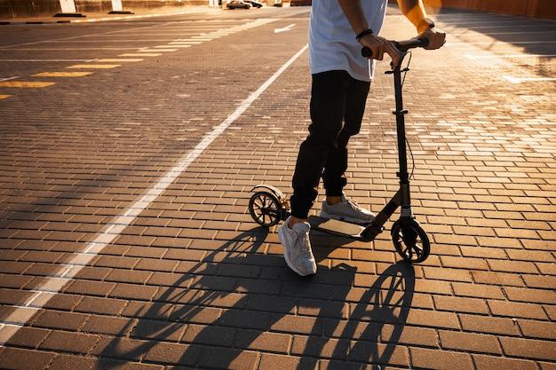 Jonge kerel gekleed in jeans en t-shirt rijdt op een scooter op het plein geplaveid met tegels in de buurt van het gebouw op de zonnige dag.