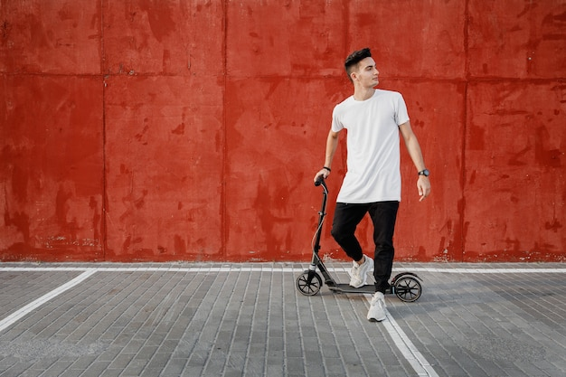 Jonge kerel gekleed in jeans en t-shirt staat met een scooter tegen een geschilderde betonnen muur op de zomerdag in de stad. .