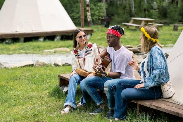 Jonge kerel in bandana zitten met meisjes in tent en mooi lied zingen op de camping