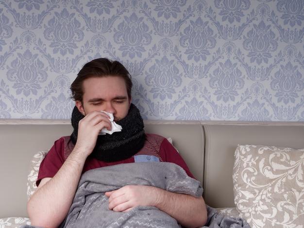 Jonge kerel in een rood t-shirt zit op het bed en zorgt voor zijn zere neus, hij heeft een loopneus, het concept van ziekte thuis