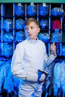 Jonge kerel in een schermpak met een zwaard in zijn hand, op een blauwe achtergrond, neonlicht. de atleet traint. sport, jeugd, gezonde levensstijl.