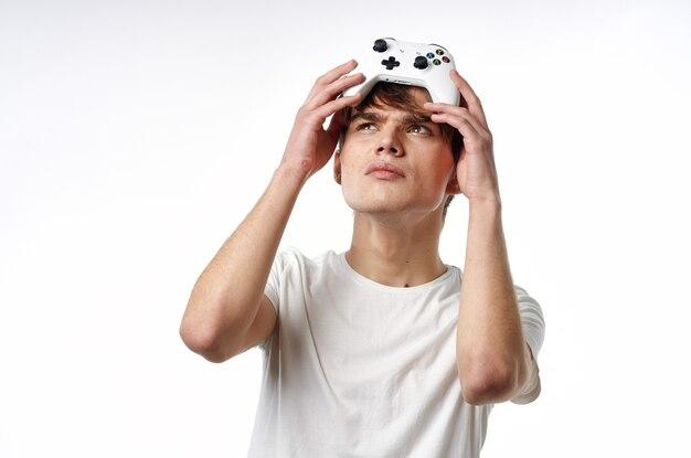 Jonge kerel in een witte t-shirtjoystick in de handen van de lichte achtergrond van spelemoties