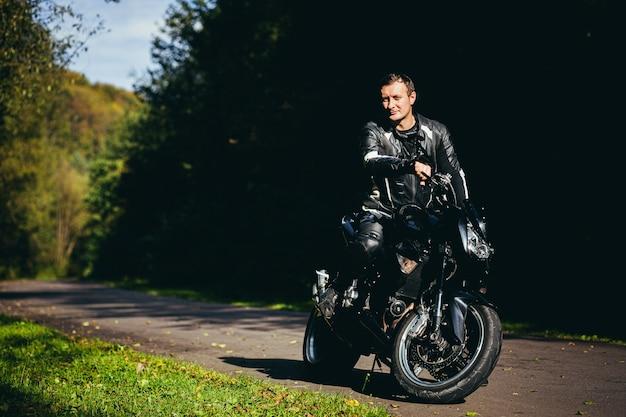 Jonge kerel in een zwart leren jas, zittend op een sportieve motorfiets op de achtergrond van een prachtige bosweg