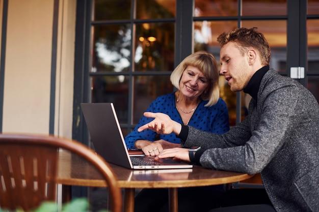 Jonge kerel in formele kleding heeft een zakelijk gesprek met oude vrouw in café.