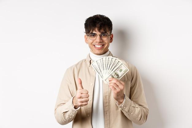 Jonge kerel in glazen die dollarbiljetten en duimen tonen omhoog, geld verdienen, die zich met contant geld op witte muur bevinden.