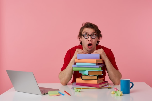 Jonge kerel in glazen, in rood t-shirt, zit bij de tafel en werkt met laptop en boeken, leunde op een stapel boeken, kijkt geschokt en verrast met wijd open mond. geïsoleerd op roze achtergrond.