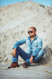 Jonge kerel in jeanskleren die op het zand in maleisië liggen