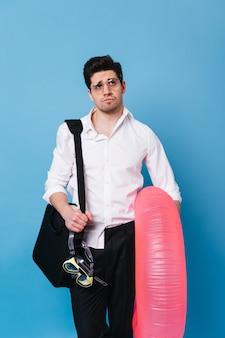 Jonge kerel in zakelijke stijl jurk wordt bedachtzaam opgezocht. de mens houdt roze opblaasbare cirkel op blauwe ruimte.