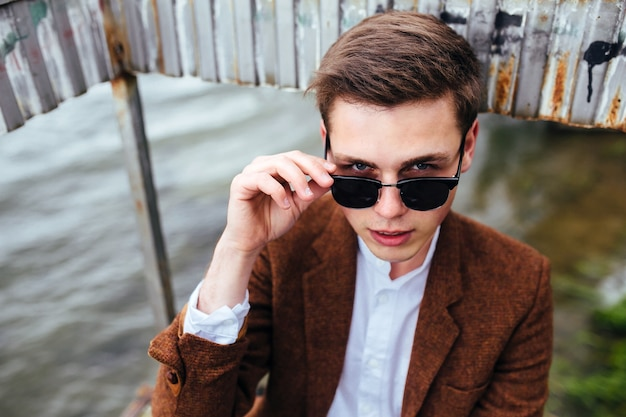 Jonge kerel in zonnebril die zich voordeed op de pier