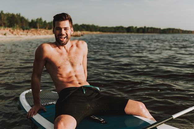 Jonge kerel in zwempak die op branding in water rusten.