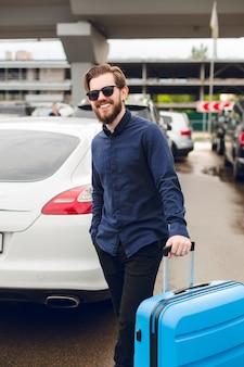 Jonge kerel met baard in zwarte zonnebril staat met koffer op parkeerterrein in luchthaven. hij draagt een zwart shirt met broek en lacht naar de camera.